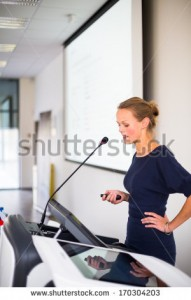 stock-photo-pretty-young-business-woman-giving-a-presentation-in-a-conference-meeting-setting-shallow-dof-170304203