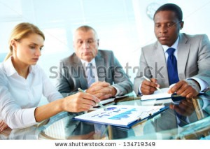 stock-photo-pretty-secretary-pointing-at-paper-while-explaining-something-to-her-boss-and-colleague-134719349